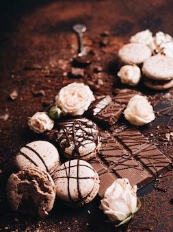 Barra de chocolate y sirope sobre los macarrones con rosas.