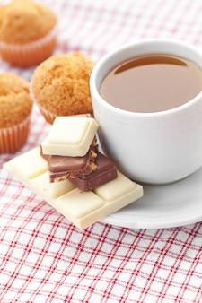 Barra de chocolate, té y muffin sobre tela a cuadros.