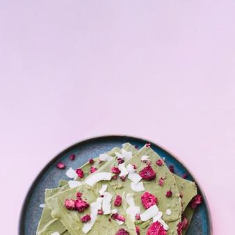 Barra de chocolate verde con frambuesas secas en un plato sobre fondo púrpura