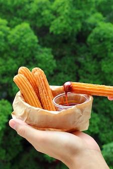 Barra de churro delicioso después de sumergir en salsa de caramelo
