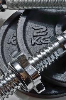 Barra y discos negros de una mancuerna plegable con designación de peso. de cerca.