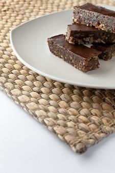 Barra de energía vegetariana de chocolate sin gluten sobre fondo blanco.