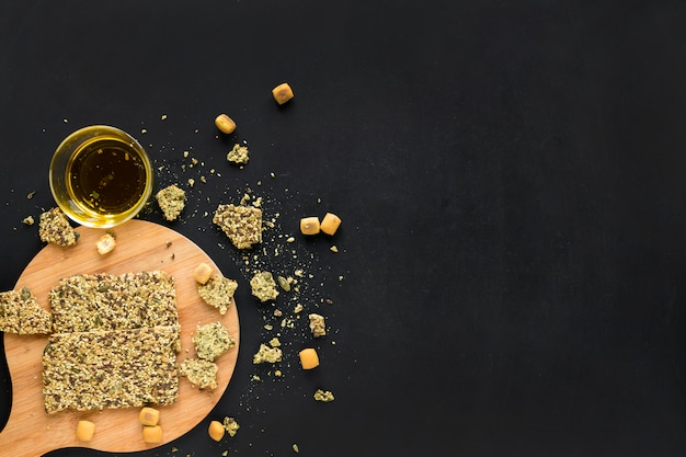 Barra de granola con aceite sobre tabla de cortar de madera