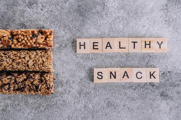 Barra de granola. barra de cereales granola con nueces, chocolate. letras de madera palabras texto saludable snack bars