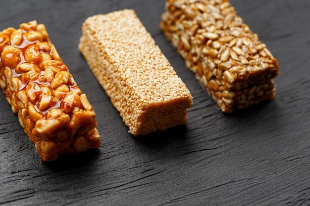Barra de granola de cereales con maní, ajonjolí y semillas de girasol sobre una tabla para cortar sobre una mesa de piedra oscura. vista desde arriba. tres barras surtidas