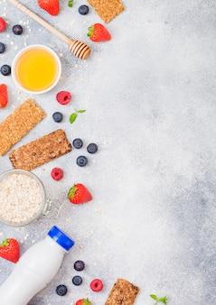 Barra de granola de cereales orgánicos con bayas con cuchara de miel y tarro de avena y botella de bebida de leche. vista superior. fresa, frambuesa y arándano con nueces almendras.