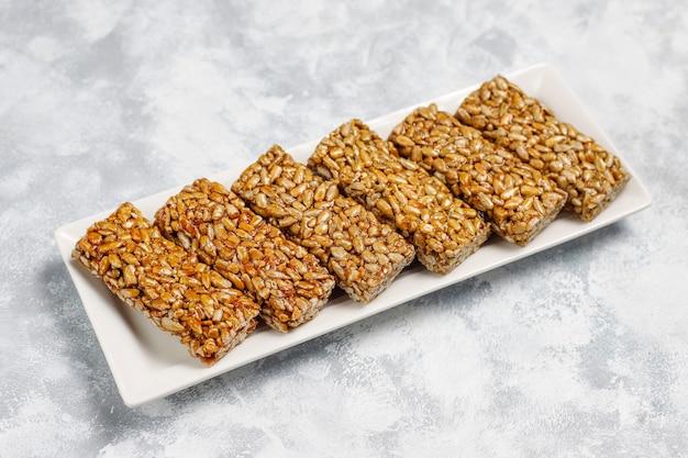 Barra de granola. merienda saludable postre dulce. sésamo, maní, girasol en miel. gozinaki es comida nacional georgiana, dulce oriental. vista superior sobre hormigón