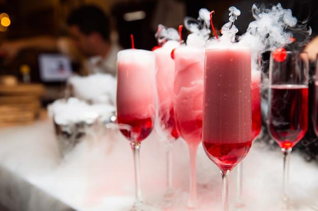En la barra hay vasos con una bebida roja. el humo sale del cristal. el vaso está decorado con cerezas.