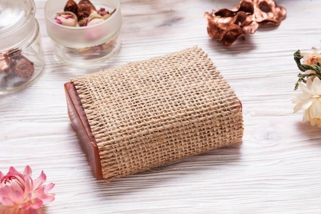 Barra de jabón casero envuelto en tela de cáñamo sobre fondo de madera