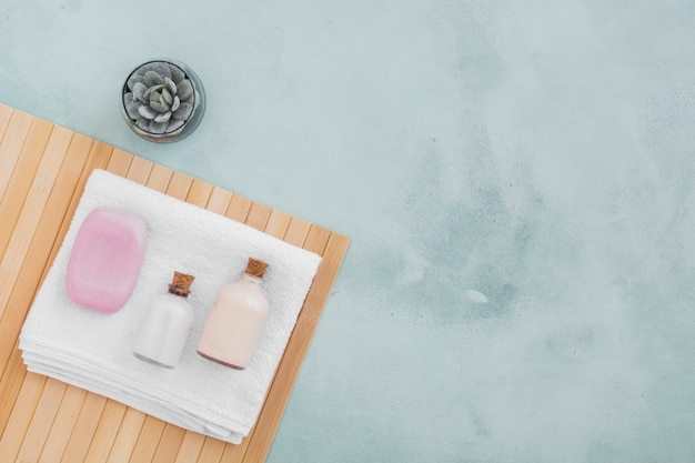 Barra de jabón y productos de baño en una toalla con espacio de copia