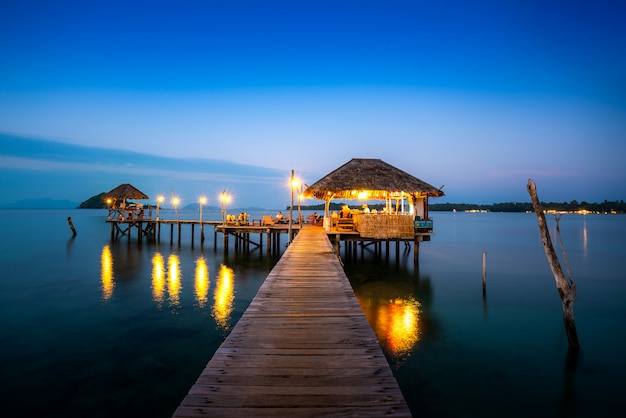 Barra de madera en el mar y choza con el cielo nocturno en koh mak en trat, tailandia. verano, viajes, vacaciones y vacaciones.