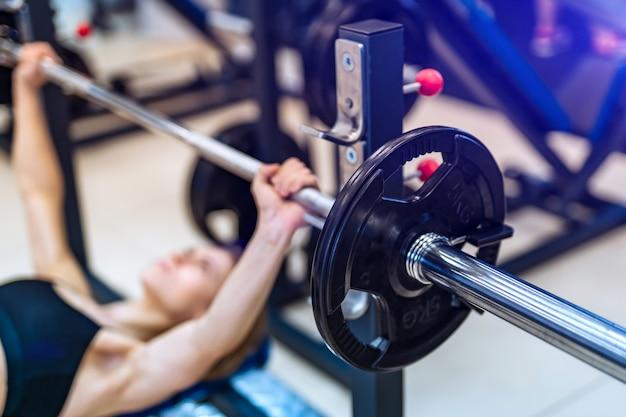 Barra de metal está levantando por joven tumbado en un banco en el interior en el gimnasio.