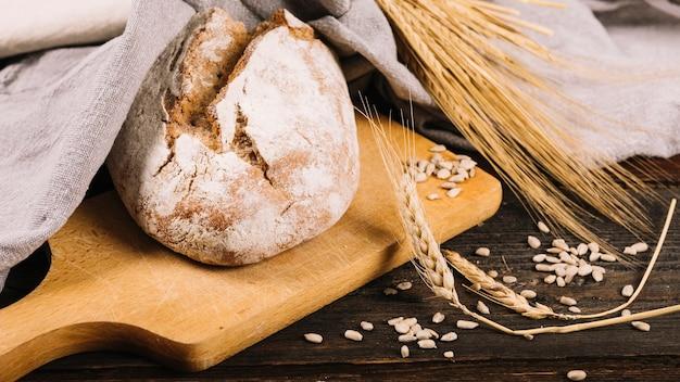 Barra de pan y espiga de trigo sobre fondo de madera oscuro