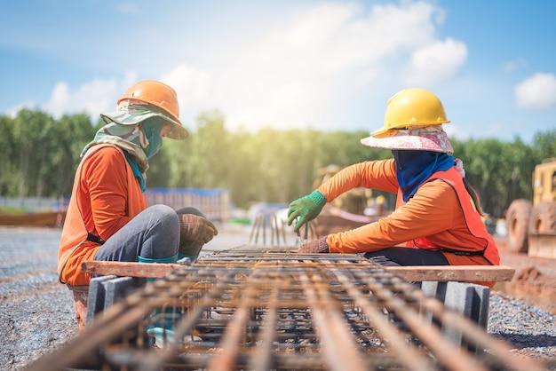 Barra de refuerzo de acero del ensamblaje del trabajador para la columna en el sitio de construcción tailandia.
