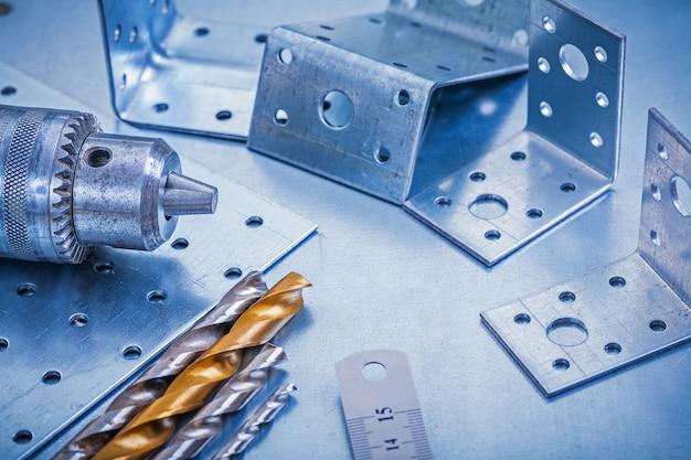 Barras angulares perforadas regla taladro de regla de chapa y brocas en concepto de construcción de fondo metálico