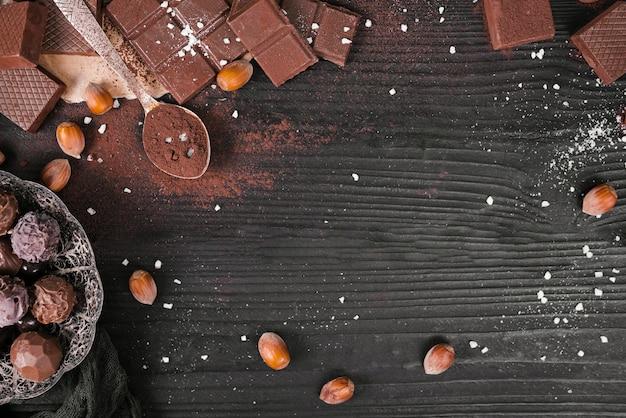 Barras de chocolate de alto ángulo y cuchara con cacao en polvo y espacio de copia
