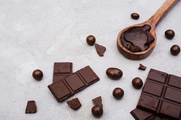 Barras de chocolate de alto ángulo y cuchara de madera con jarabe de chocolate
