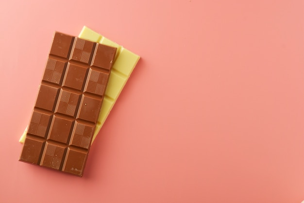 Barras de chocolate blanco y negro sobre rosa