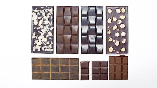Barras de chocolate con nueces sobre un fondo blanco. hecho a mano.