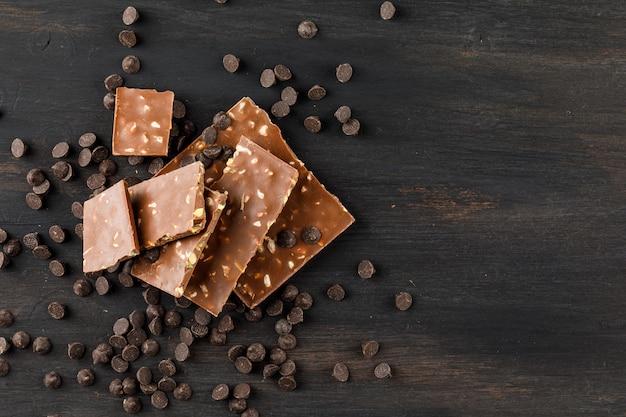 Barras de chocolate con pistacho y choco gotas vista superior sobre un fondo oscuro