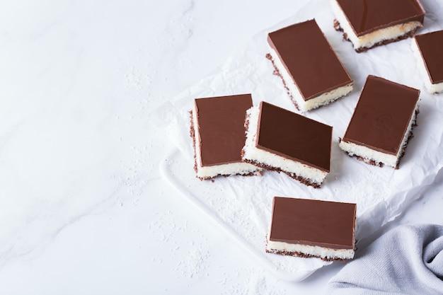Barras de coco veganas crudas orgánicas de energía saludable caseras con chocolate en una mesa de cocina