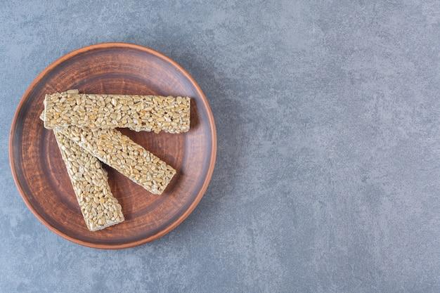 Barras de granola en una placa de madera, sobre la superficie de mármol