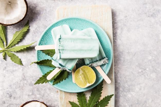 Barras de helado con rodajas de coco, cannabis en el fondo de hormigón.