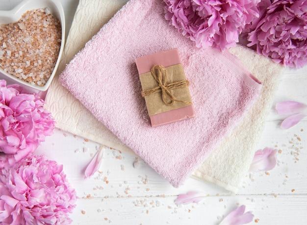 Barras de jabón artesanal, toallas suaves y flores de peonía.