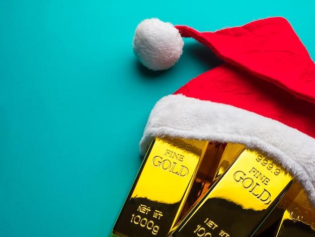 Barras de oro como regalo de navidad con gorro de papá noel sobre fondo verde.