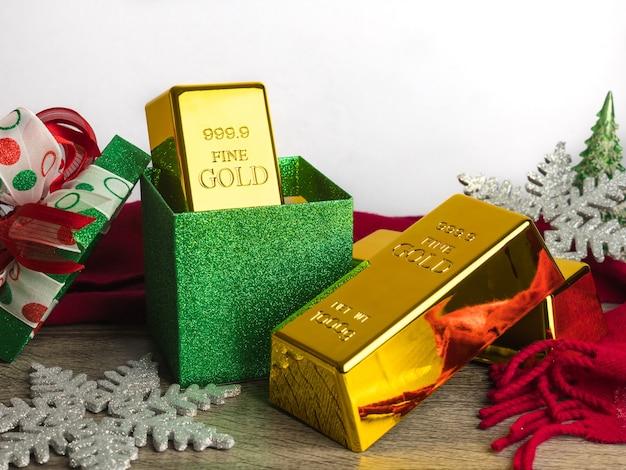 Barras de oro como regalo de navidad en la mesa de madera con adornos.