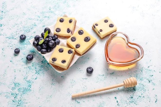 Barras de tarta de arándanos con miel y bayas frescas