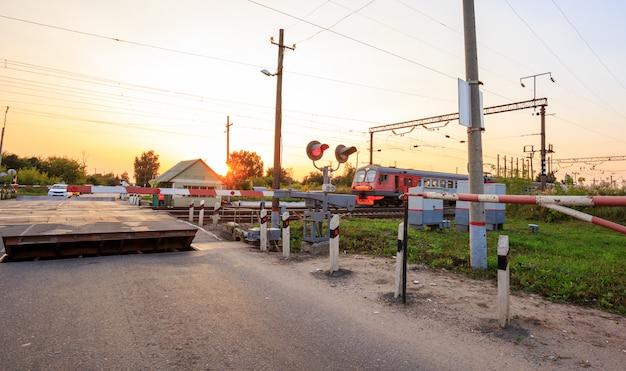 Barrera de cruce ferroviario, semáforos y señales de joroba en el paisaje rural