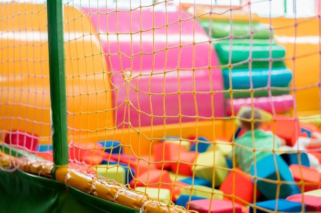 Barrera de rejilla textil de un foso con cubos blandos para niños en el interior del parque infantil. interior. agujero