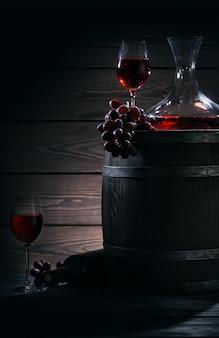 Barril, jarra y copas con vino tinto en una bodega oscura