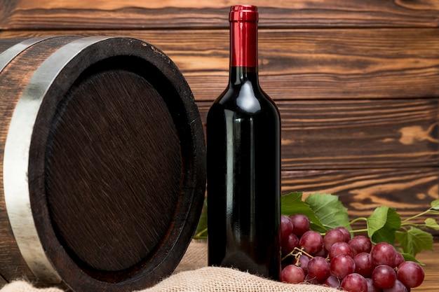 Barril de madera con botella y vaso de vino