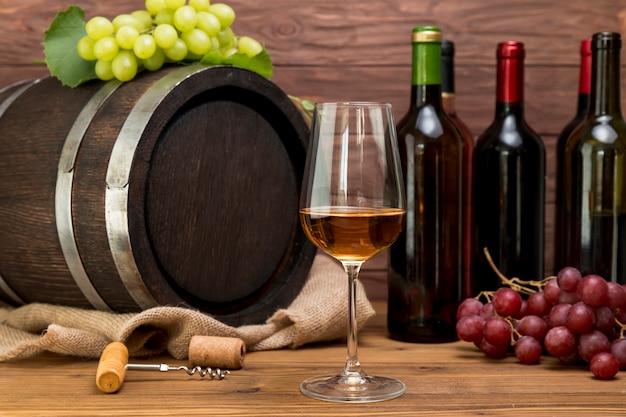 Barril de madera con botellas y vasos de vino