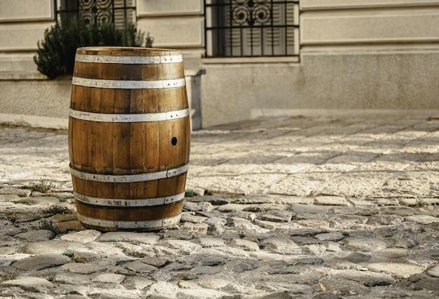 Barril de madera sobre el pavimento delante de un buili