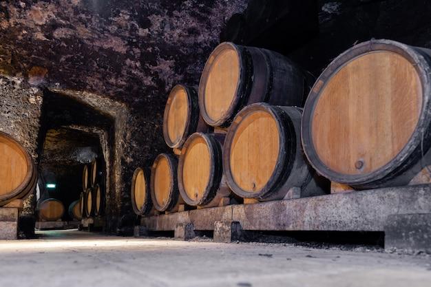 Barriles gigantes de madera de roble de vino apilados en filas