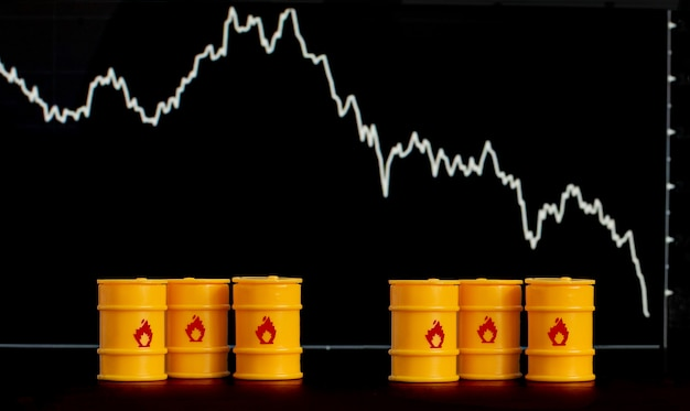 Barriles de petróleo y gasolina en el fondo de una pantalla con un gráfico descendente