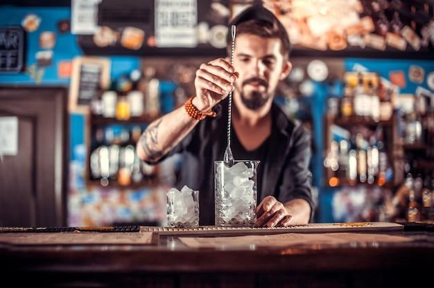 Bartender centrado vertiendo bebida alcohólica fresca en los vasos en el pub