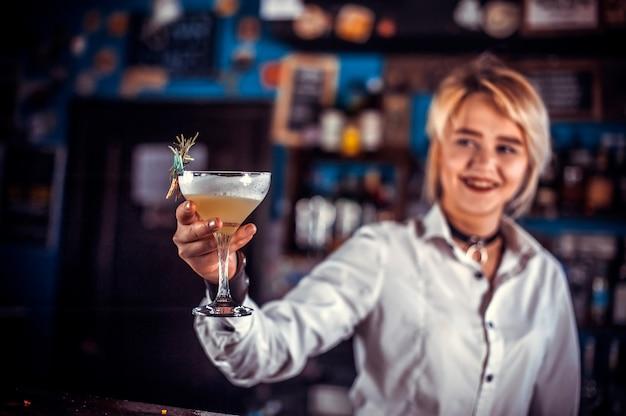 Bartender chica crea un cóctel en la cervecería