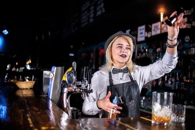 Bartender chica experta decora brebajes coloridos en bar de cócteles