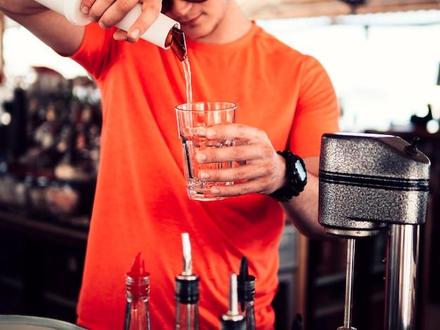 Bartender masculino relleno de vaso con bebida clara