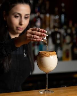 Bartender mujer agregando canela en polvo en un cóctel lechoso.