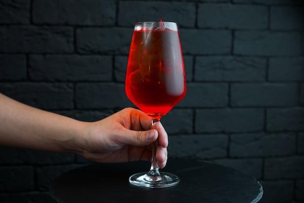 El bartender ofrece un delicioso cóctel de cerezas dulces en una copa elegante con el agregado de vodka con jugo natural con jarabe de plátano y ron blanco. la bebida se sirve fría. fiesta en el resto