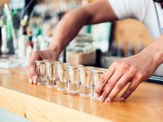 Bartender poner fila de vasos de chupito en mostrador