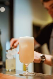 Bartender preparando gin-tonic con pepino de fondo, cóctel de piña colada en primer plano. foto con poca profundidad de campo. imagen de estilo de vida vertical.