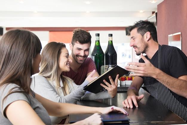 Bartender que muestra el menú al cliente en el bar