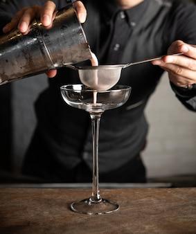 Bartender verter coctelera y colador de vidrio en barra de bar