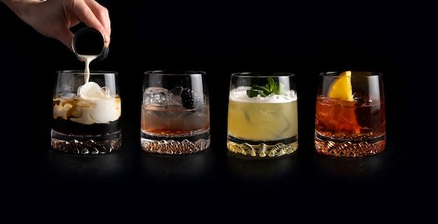 Bartender vierte crema y prepara un conjunto de cócteles alcohólicos clásicos white russian, bramble, whisky sour y negroni.